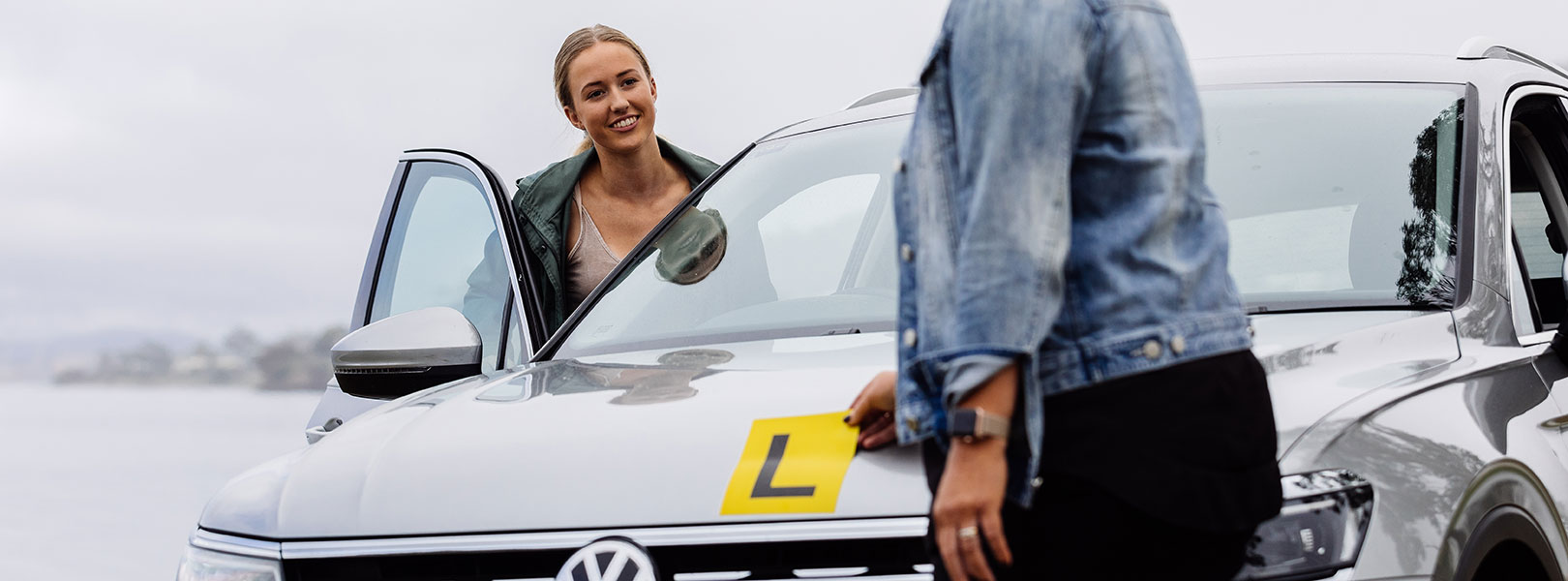 Young lady getting into the driver's seat of a car with L Plates displayed