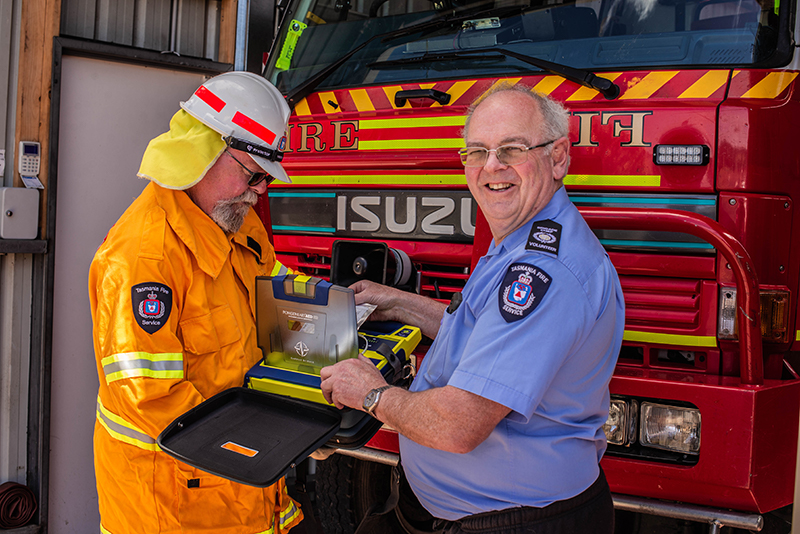 Two fire fighters looking at a defibrillator