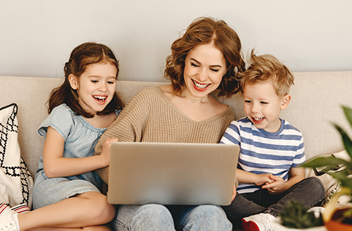 Mother on computer with two children