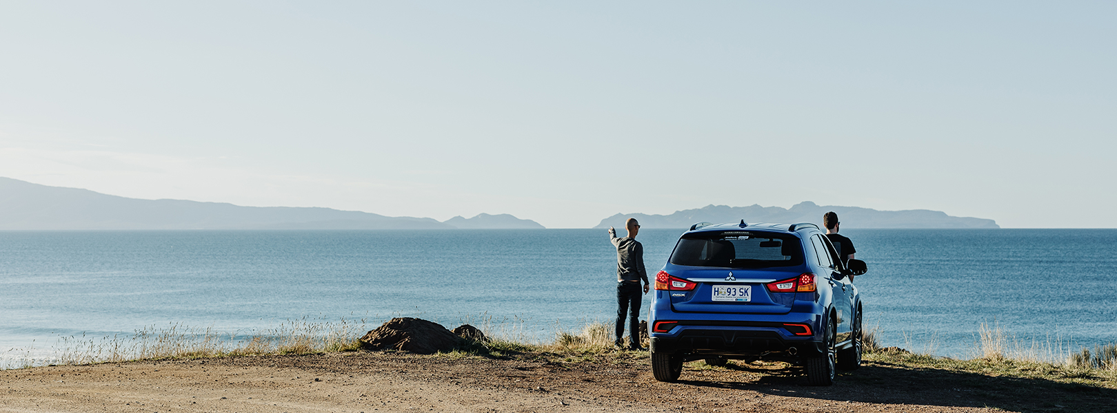 Couple standing next to an SUV looking out towards the ocean