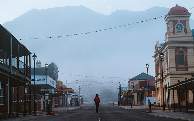 Lady standing in middle of deserted street in foggy Queenstown