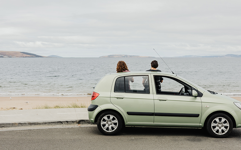 Two people standing beside a green car looking at the ocean