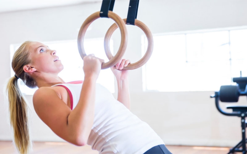 Woman doing pull ups with gym equipment