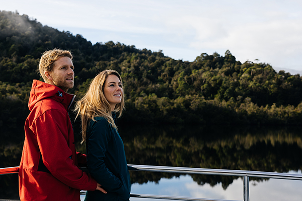 Man and woman on boat overlooking river and rainforest
