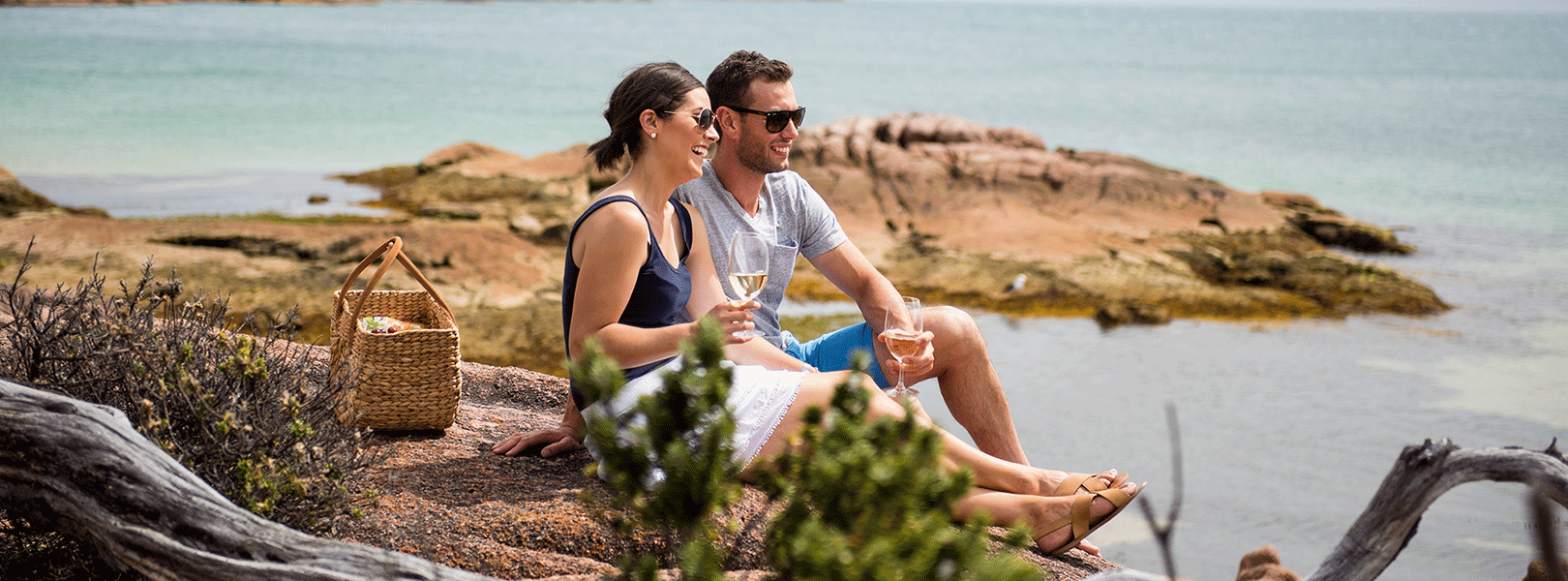 Couple picnicking on beach at Freycinet Lodge
